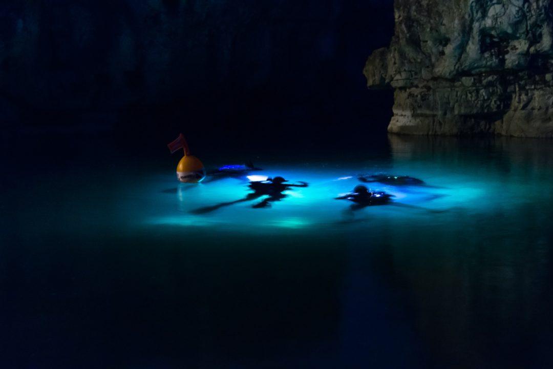 Taucher nachts im Meer mit Taschenlampen